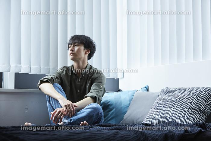 ベッドの上でくつろぐ日本人男性の販売画像