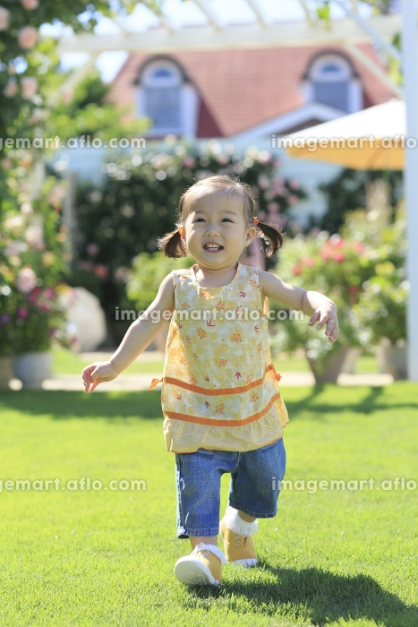 芝生とバラのある広い庭を走る女の子