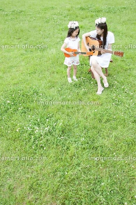 草原で楽器を演奏する女性と女の子の販売画像