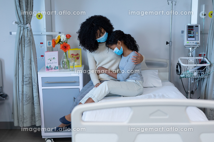 Mixed race mother comforting sick daughter sitting on hospital bed, both wearing face masks. medicine, health and healthcare services during coronavirus covid 19 pandemic.の販売画像