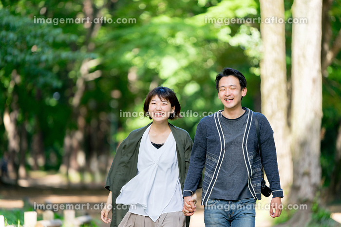 デートで新緑の爽やかな小道を散歩するカップルの販売画像