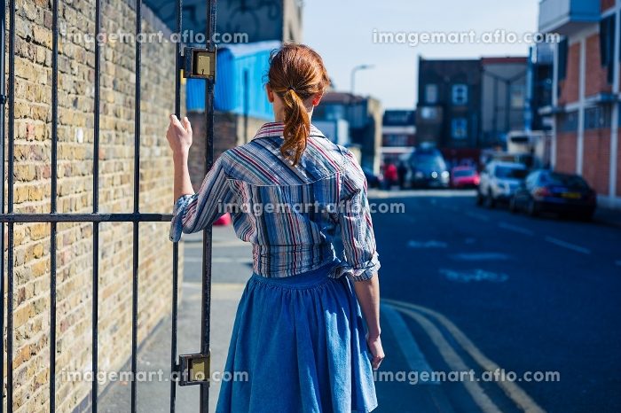 A young woman is standing in the street and is resting her hand on a metal gateの販売画像