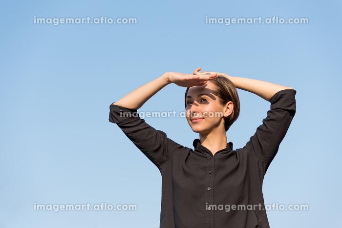 青空の下でリラックスする若い女性の販売画像