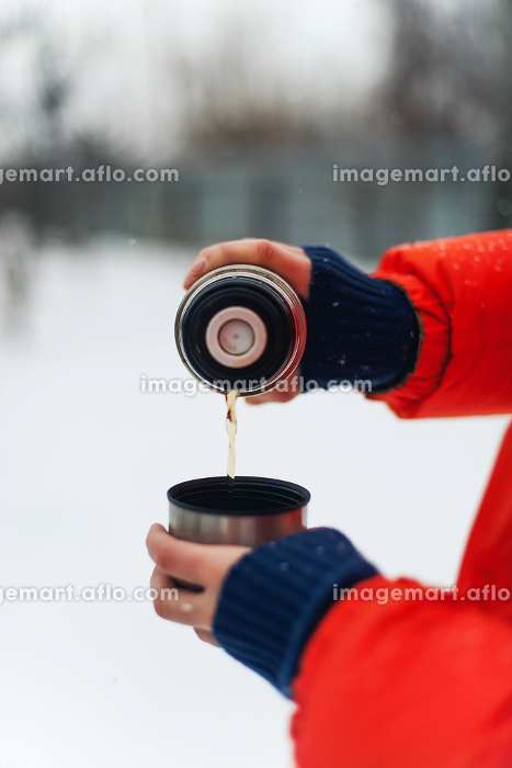 Woman in orange jacket  pouring herself a warm cup of hot tea ouの販売画像