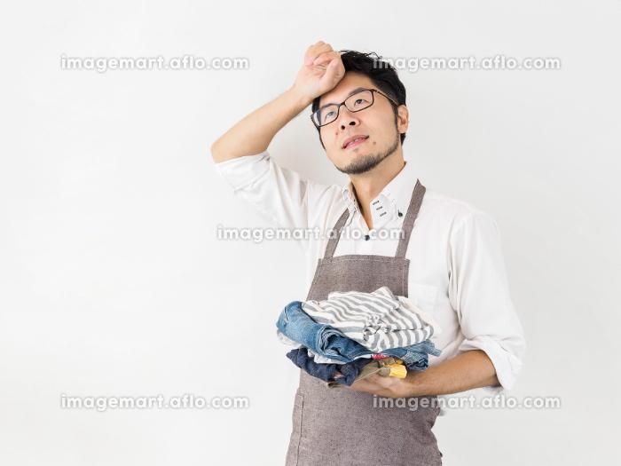 洗濯物をたたむ男性のイメージの販売画像