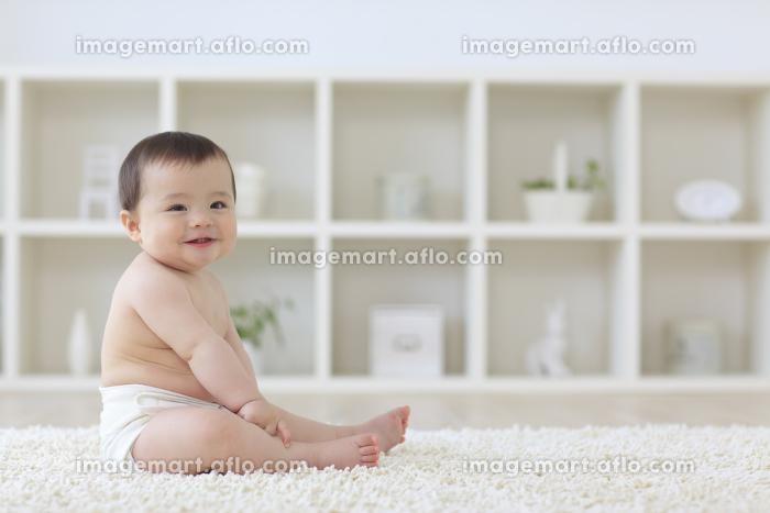 リビングに座っている笑顔のハーフの赤ちゃんの販売画像