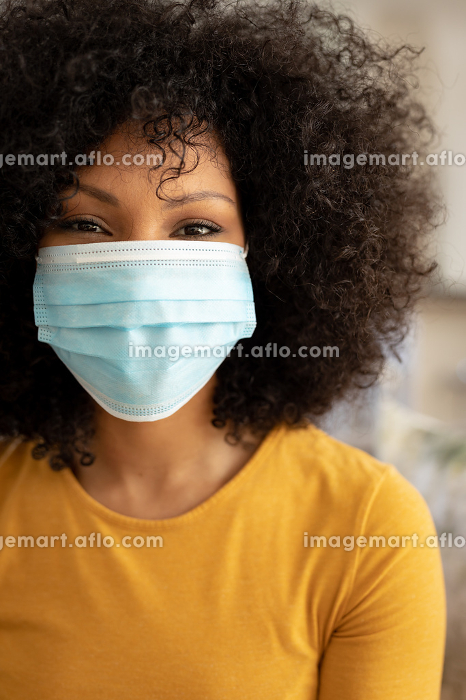 Portrait of African American woman with afro hair at home, wearing a mask and looking to camera. Social distancing and self isolating at home during Coronavirus Covid 19 quarantine lockdown.の販売画像