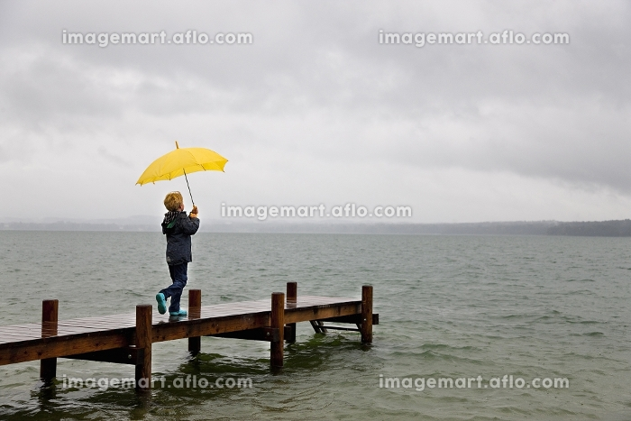 桟橋で傘を持つ少年の販売画像
