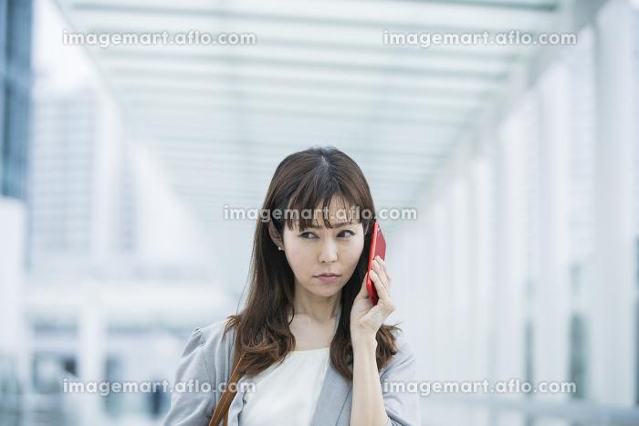 困った表情で電話するビジネスウーマンの販売画像