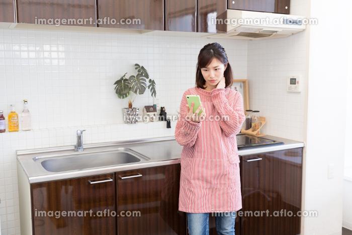 キッチンでスマホを見る女性 考えるの販売画像