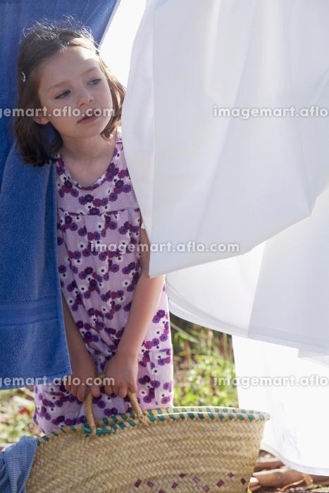 Young girl looking through washingの販売画像