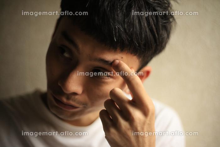 眉を掻く男性の販売画像