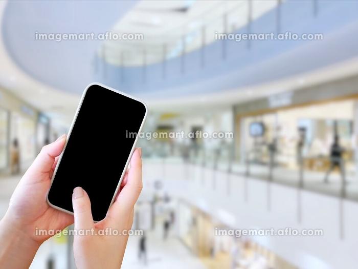 ショッピングモールでスマホを触る女性の販売画像