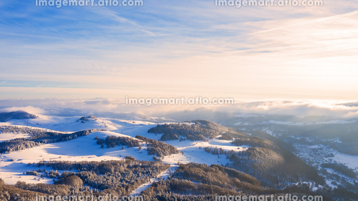 Aerial view of a gold sunset over winter snow.の販売画像
