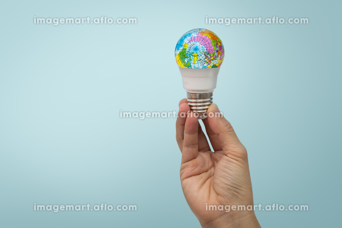 Hand is holding the LED bulb with the globe on blueの販売画像
