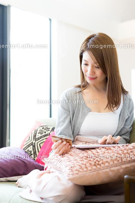 ネットショッピングの決済をする女性の販売画像