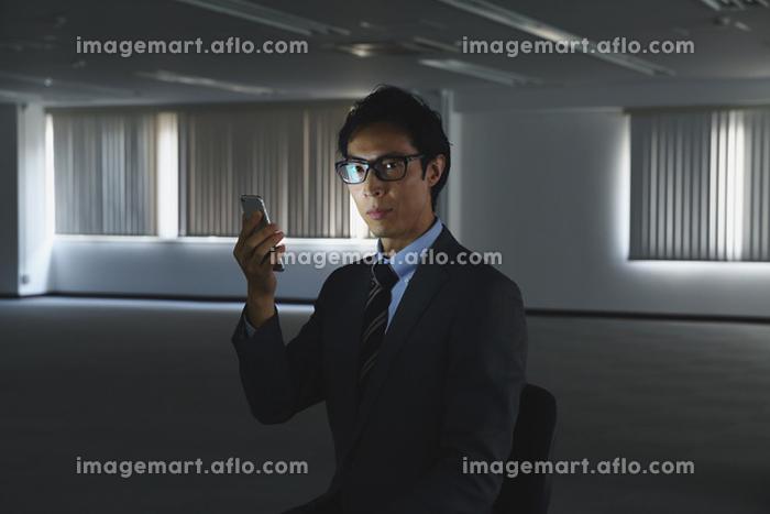暗いオフィスでスマートフォンを見る日本人ビジネスマン
