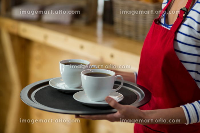 Mid-section of waitress standing with cup of coffee