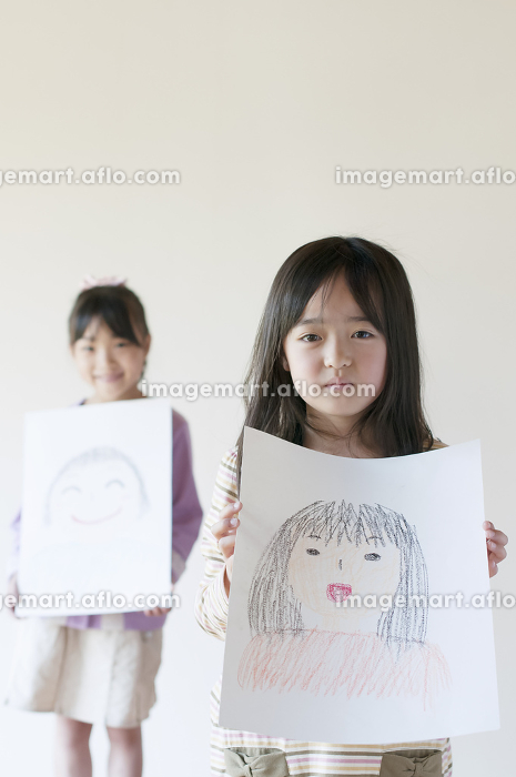 自分の描いた絵を見せる2人の女の子の販売画像