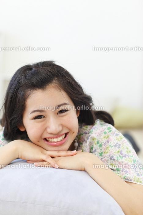 クッションに寝そべる若い女性の販売画像