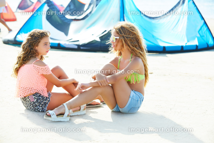 Kite surf teen girls talking in summer beach sitting on sandの販売画像