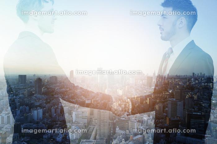 握手するビジネスマンと都市の合成写真の販売画像