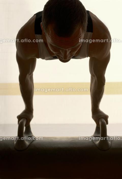 Male gymnast balancing on pommel horseの販売画像