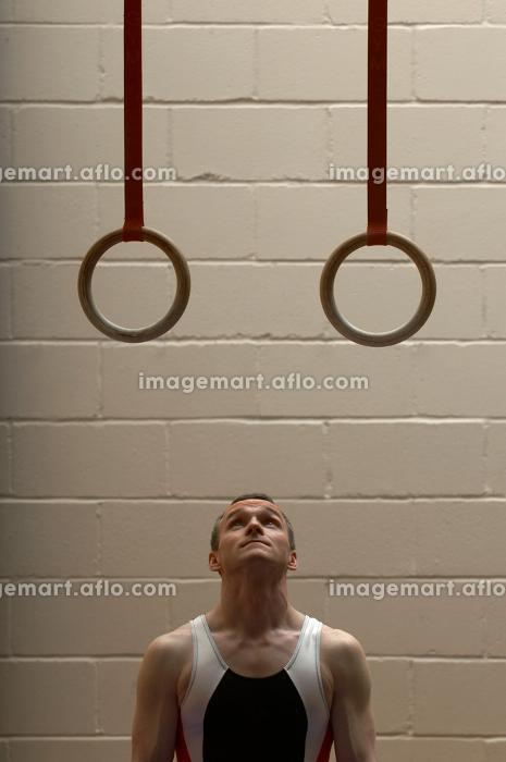 Male gymnast looking up at rings in gymnの販売画像