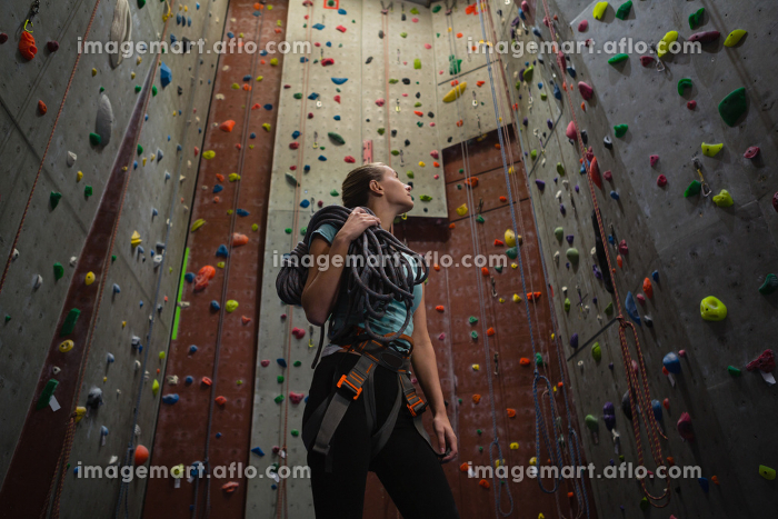 Female athlete carrying rope looking up while standing in gymの販売画像
