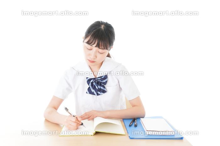 机で勉強をする制服姿の女子学生の販売画像
