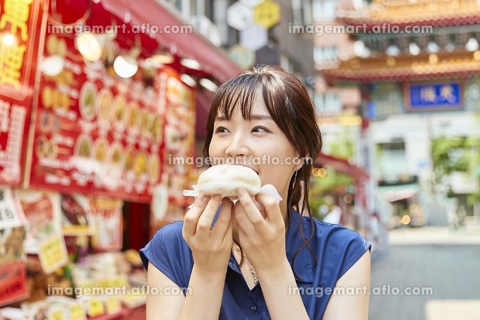 中華街で食べ歩きをする日本人女性の販売画像