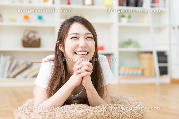 部屋でリラックスする女性の販売画像