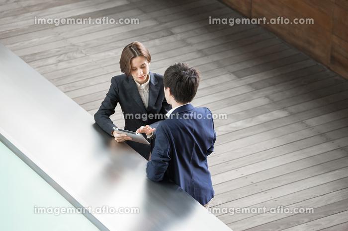 タブレットPCでミーティングする男女(ハイアングル)の販売画像
