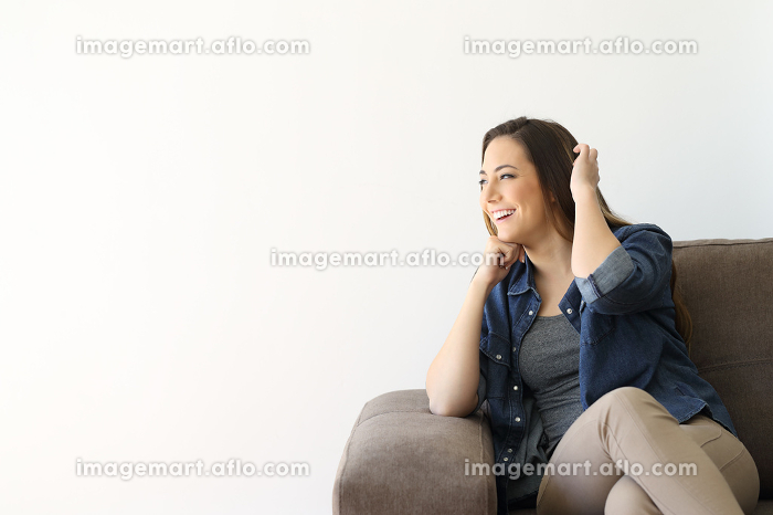 Single woman sitting on a couch looking at sideの販売画像