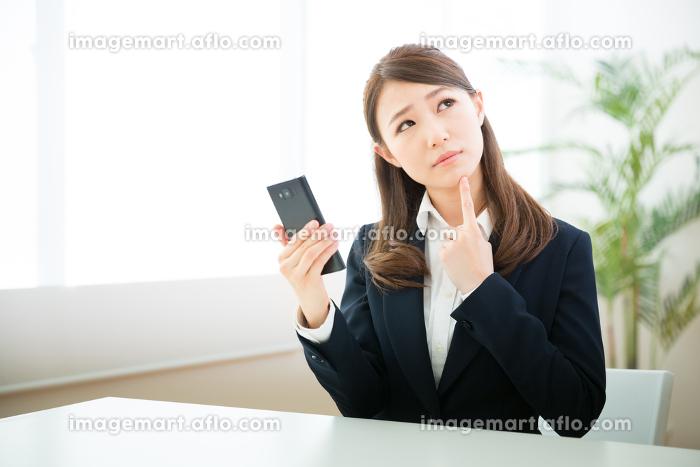 スマートフォンを見る女性 ビジネス 考えるの販売画像
