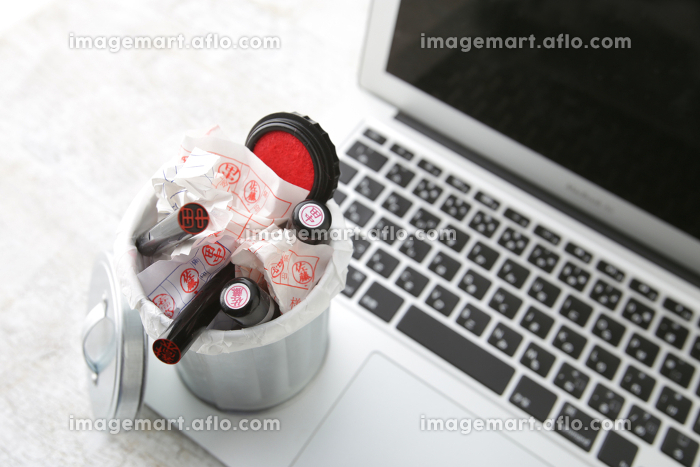ノートパソコンとゴミ箱に入れた不要になった印鑑の販売画像