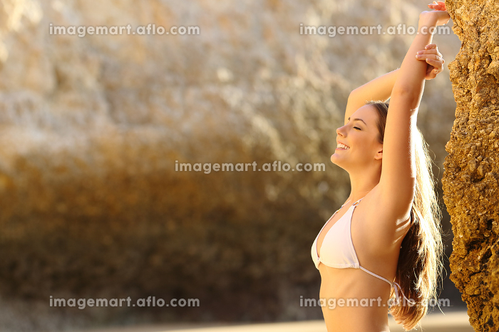 Beauty woman wearing bikini posing on the beachの販売画像