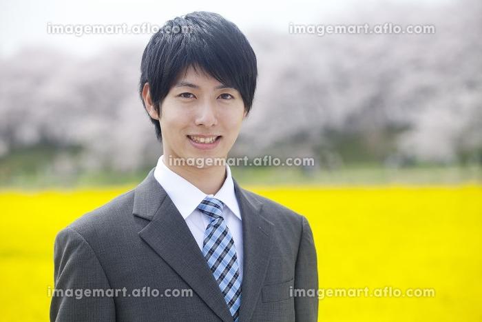 菜の花畑で微笑むビジネスマンの販売画像