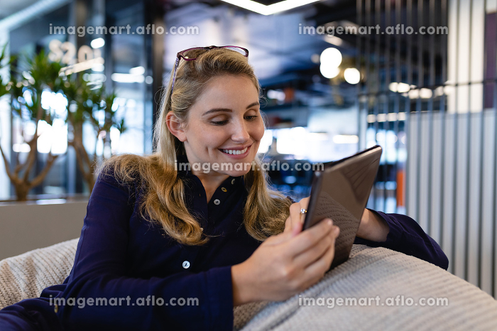 Front view of a Caucasian businesswoman wearing smart clothes, working in a modern office, sitting on a bean bag and using a tablet..の販売画像