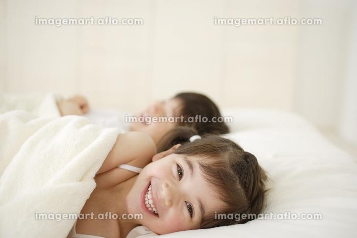 ベッドで寝転ぶハーフの女の子と男の子