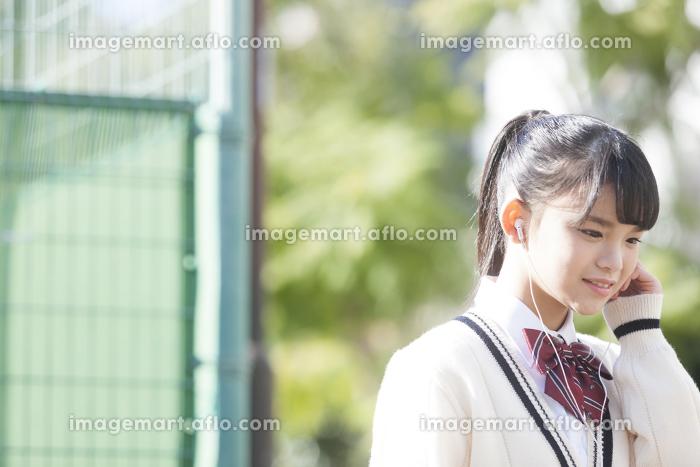 イヤホンで音楽を聴く女子校生の販売画像
