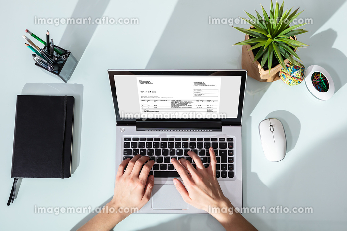 Businessperson Checking Invoice On Laptop
