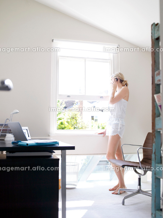 Woman on phone in sunny home officeの販売画像