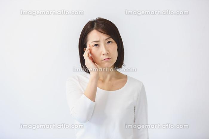 こめかみを押さえる40代日本人女性の販売画像