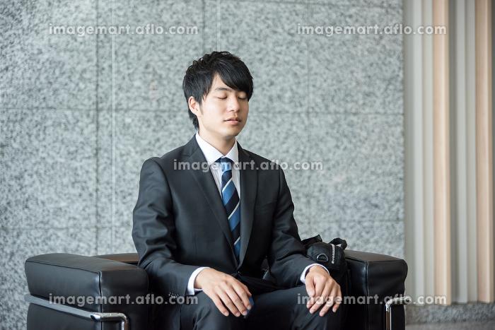 会社のロビーで座って待つ男性(目をつぶる)の販売画像