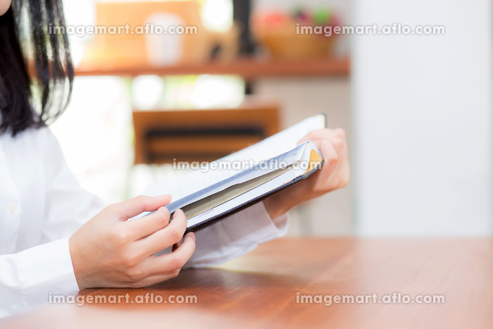 Closeup business woman reading on notebook on table, girl work aの販売画像