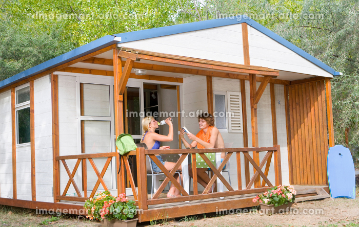 Young couple relax on cabin summer terrace