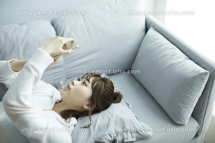 寝ながらスマホを見る日本人女性