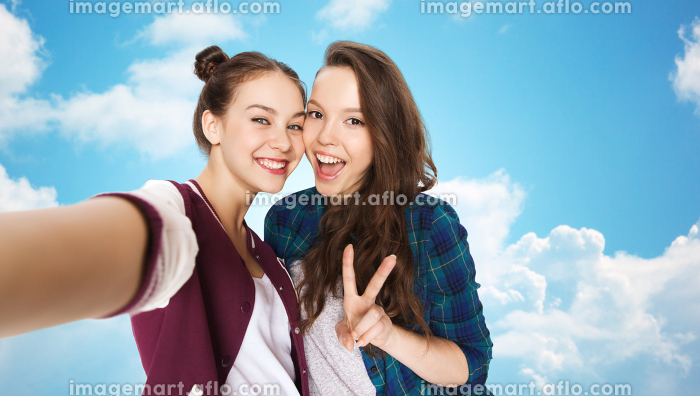 happy friends taking selfie and showing peaceの販売画像