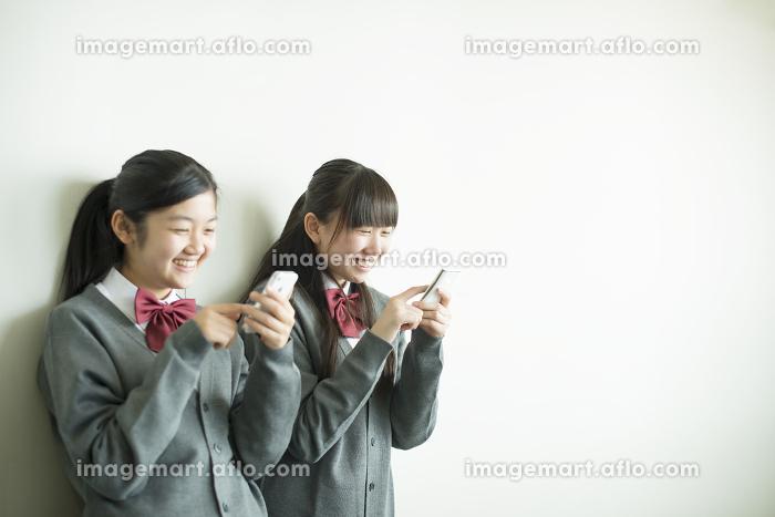 スマートフォンを操作する中学生の販売画像